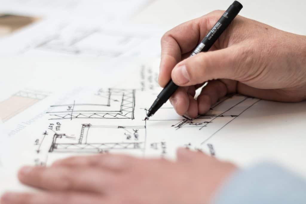 man with pen drawing on an architectural plan.